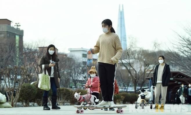 휴일인 24일 오후, 서울 최고기온이 13.9까지 오르는 등 겨울 같지 않는 따뜻한 날씨 속에 송파구 송파둘레길의 한 코스인 성내천길을 따라 많은 시민들이 마스크로 단단히 무장한 가운데 산책을 즐기고 있다. 한 소녀가 롱보드에 애완견을 태우고 산책길을 달리고 있다.