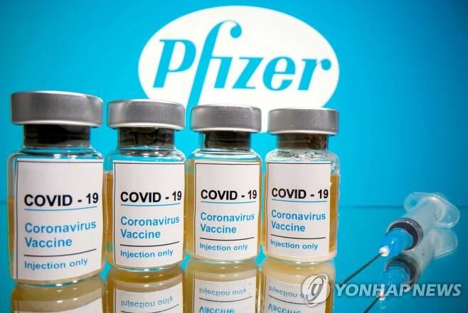 미국 제약사 화이자 로고 앞으로 신종 코로나바이러스 감염증(코로나19) 백신이라고 쓰인 병이 놓여있다. [로이터=연합뉴스 자료사진]