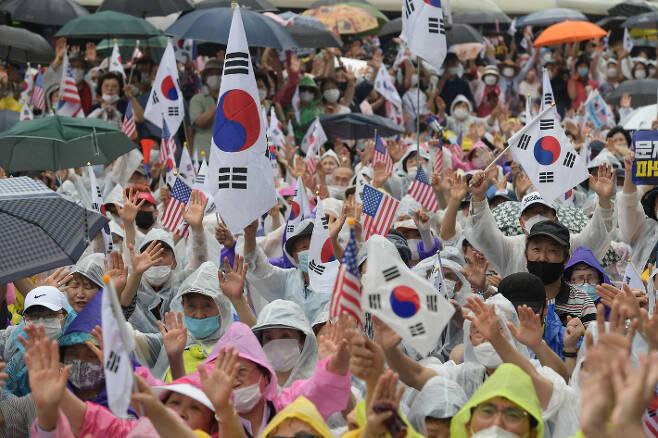 지난해  8월 15일 오후 서울 종로구 동화면세점 앞에서 열린 보수단체의 광복절 집회에서 참석자들이 태극기와 성조기를 흔들고 있다. 이한형 기자