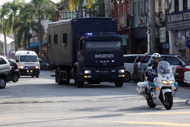 말레이시아 이민당국 호송 차량이 23일 미얀마인 본국 송환을 위해 루무트 해군기지로 이동하고 있다. 루무트=로이터 연합뉴스