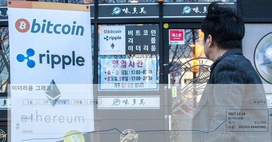 경기도 일산 장항동의 한 음식점 앞에 비트코인과 리플, 이더리움 등 가상화폐로 결제가 가능하다고 알리는 입간판이 보이고 있다. 뉴스1