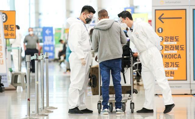 모든 해외 입국자를 대상으로 유전자증폭(PCR) 검사 음성확인서 제출 의무화 제도가 시행된 24일 오전 인천국제공항 제1여객터미널에서 방역 관계자가 입국자를 안내하고 있다. 연합뉴스