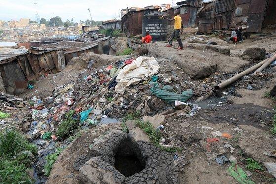 지난해 11월 케냐 나이로비의 마타레 빈민가에서 어린이들이 부서진 하수도 맨홀 옆에서 놀고 있다. 유엔은 전 세계 인구 가운데 42억명은 안전하게 관리되는 위생 시설에 접근 할 수 없다고 밝히고 있다. EPA=연합뉴스
