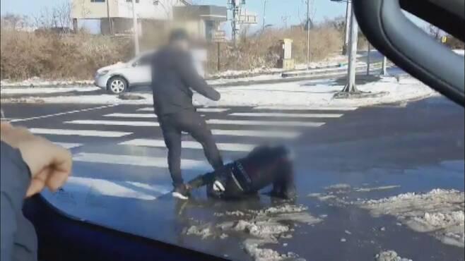 쓰러진 오토바이 운전자를 향해 40대 남성이 발길질하고 있다