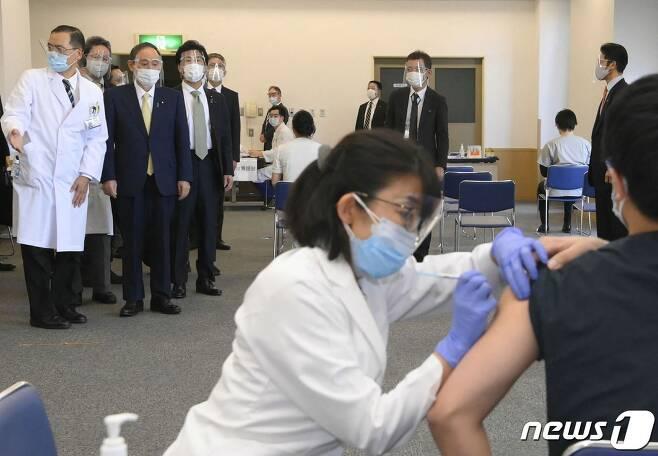 스가 요시히데 일본 총리가 18일 (현지시간) 국영 도쿄 메디컬 센터에서 코로나19 화이자 백신 접종 모습을 지켜보고 있다, © AFP=뉴스1 © News1 우동명 기자