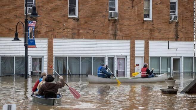 홍수가 난 도시를 보트로 이동하는 미국 켄터키주 주민들