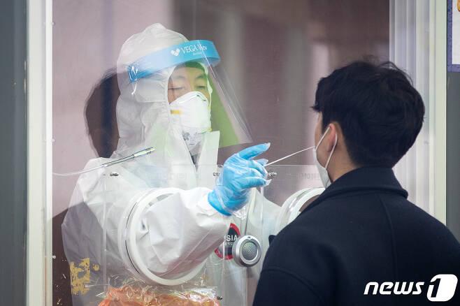 3일 서울역 광장에 마련된 신종 코로나바이러스 감염증(코로나19) 임시선별검사소에서 관계자가 한 시민의 코로나19 검체를 채취하고 있다. 2021.3.3/뉴스1 © News1 유승관 기자