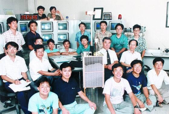 소형 인공위성시대를 연 우리별 제작팀이 우리별 실물크기 모형을 중심으로 위성지구국에 함께 모였다. 모형 바로 우측이 최순달 인공위성센터 소장이다. 이들은 쎄트렉아이를 창립해 세계적 위성 업체로 키웠다.