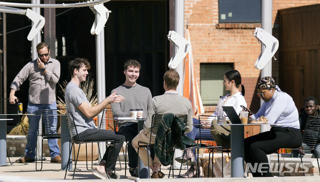 [댈러스=AP/뉴시스]지난 3일(현지시간) 미국 텍사스주 댈러스에 있는 카페 야외 테이블에서 사람들이 마스크를 착용하지 않은 사람들이 대화를 나누고 있다. 2021.03.08.
