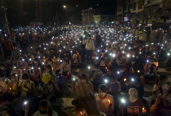 미얀마 최대 도시 양곤에서 14일(현지시간) 통행금지 이후에도 시민들이 휴대전화 불빛을 비추며 군부 쿠데타 규탄 시위를 벌이고 있다. 미얀마 정치범지원협회(AAPP)는 이날 하루 미얀마에서 시위 참가자 중 최소 38명이 군경에 의해 살해됐다고 밝혔다고 외신이 보도했다. AP=연합뉴스