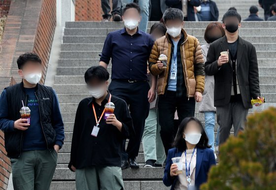 지난달 서울 명동 음식점 거리에서 점심 식사를 마친 직장인들이 커피를 들고 산책하고 있다. 뉴스1