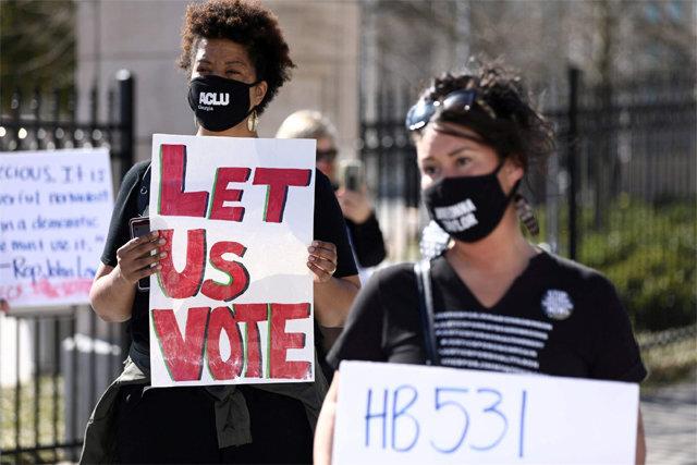 """미국 조지아주에서 흑인 투표권 제한 우려가 높은 선거법 개정안이 통과되자 흑인 인권단체 회원들이 """"우리에게 투표권을 달라""""며 피켓 시위를 벌이고 있다. NBC 뉴스 화면 캡처"""