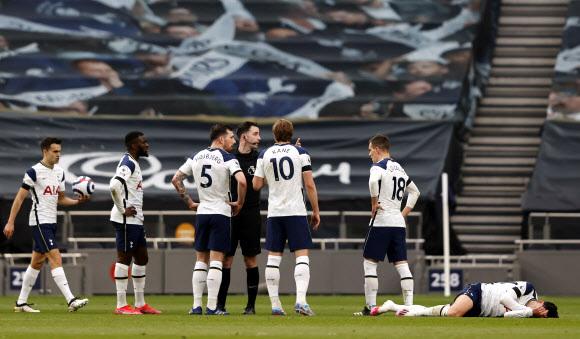 잉글랜드 프로축구 토트넘 홋스퍼의 손흥민(오른쪽)이 12일(한국시간) 영국 런던 토트넘 홋스퍼 스타디움에서 열린 맨체스터 유나이티드와의 홈 경기에서 스콧 맥토미니를 수비하다 얼굴을 가격당한 뒤 그라운드에 쓰러져 있다.런던 로이터 연합뉴스
