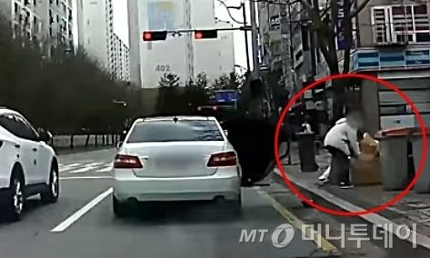 경기 파주시의 도로에서 한 운전자가 차에서 내린 뒤 차에 있던 쓰레기를 꺼내 버리고 있다./사진=유튜브 '한문철TV'