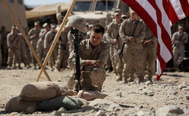 미 해병대원들이 아프간 남부 헬만드주에서 탈레반과 교전 도중 전사한 동료를 추모하고 있다. AP·연합뉴스
