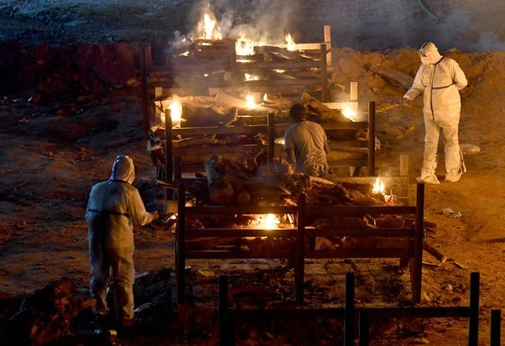 2일(현지시간) 인도 벵갈루루 지역의 한 화장장에서 코로나19 방역복을 입은 직원들이 밤 늦은 시간에도 밀려드는 시신을 화장하고 있다. [로이터=연합뉴스]