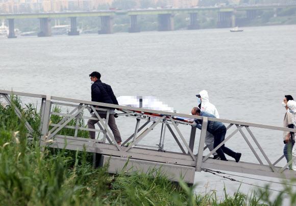 지난달 30일 오후 서울 반포한강공원 인근 한강에서 구조대원들이 실종 엿새 만에 숨진 채 발견된 대학생 손정민씨의 시신을 수습하고 있다. 연합뉴스