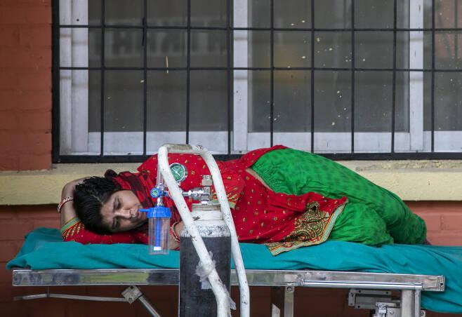 네팔 수도 카트만두의 한 병원 응급 병동 앞에서 코로나19 환자가 6일(현지시간) 의료용 산소를 공급받기 위해 기다리고 있다. 카트만두|AP연합뉴스