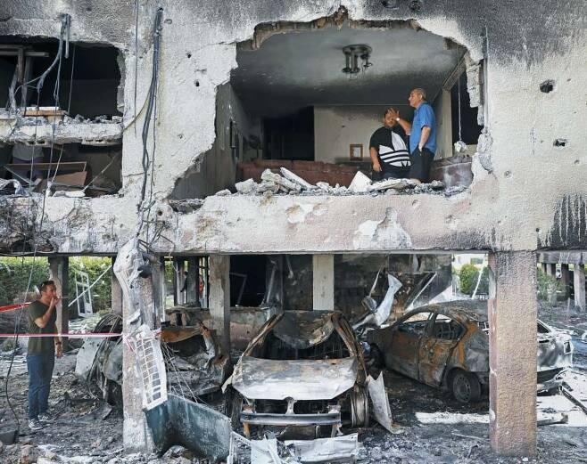 하마스 로켓포에 무너진 아파트 - 13일(현지 시각) 이스라엘 중부의 페타티크바시(市)에서 주민들이 팔레스타인 무장단체 하마스가 발사한 로켓포에 맞아 파손된 아파트 건물을 살펴보고 있다. 지난 10일 시작된 이스라엘과 하마스의 무력 충돌이 4일째 이어져 양측에서 사망자가 최소 90명 나왔다. /AP 연합뉴스