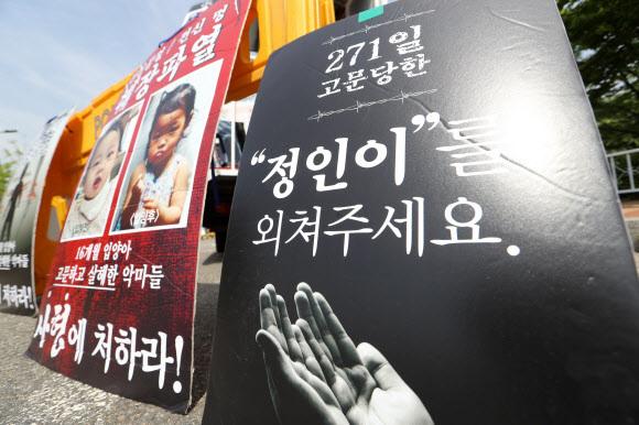 생후 16개월 된 '정인이'를 학대해 숨지게 한 혐의 등으로 기소된 정인이 양부모에 대한 1심 선고 공판이 14일 서울남부지방법원에서 열리는 가운데, 시민단체 회원들이 서울 남부구치소 앞에서 정인이 양부모 규탄 집회를 열고 있다.