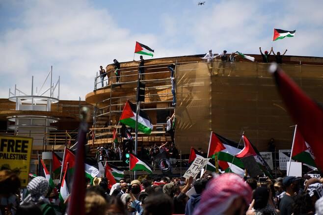 LA에서 집회에 참석한 사람들이 건물에 올라가 팔레스타인 깃발을 흔들고 있다. AFP=연합뉴스