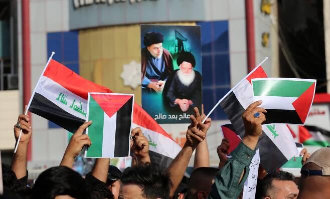 이라크 바그다드 시민들이 15일 알 타흐리르 광장에서 이라크와 팔레스타인 깃발을 들고 연대 집회를 열고 있다. EPA=연합뉴스