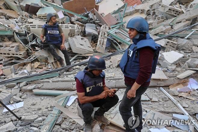 공습으로 무너진 가자지구 사무실 폐허에 앉아 있는 기자들 [AFP=연합뉴스]