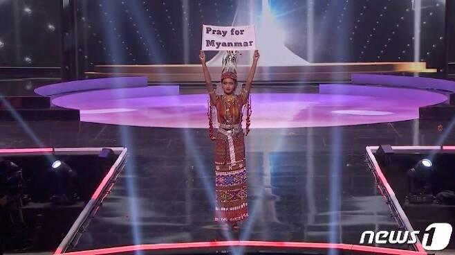2021 '미스 유니버스' 미얀마 대표 투자 윈 릿(22)이 2021년 5월13일(현지시간) 무대에서 '미얀마를 위해 기도를'(Pray for Myanmar)이라는 팻말을 들어보이고 있다/사진제공=로이터/뉴스1