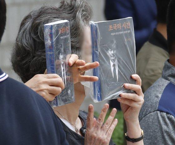 조국 전 장관이 11일 오전 서울 서초구 중앙지법에서 열린 공판에 출석하는 가운데 그의 지지자들이 신간 『조국의 시간』을 들고 조 전 장관을 응원하고 있다. 뉴스1