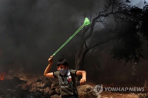 이스라엘군에 돌팔매질하는 팔레스타인 소년 [AFP=연합뉴스]