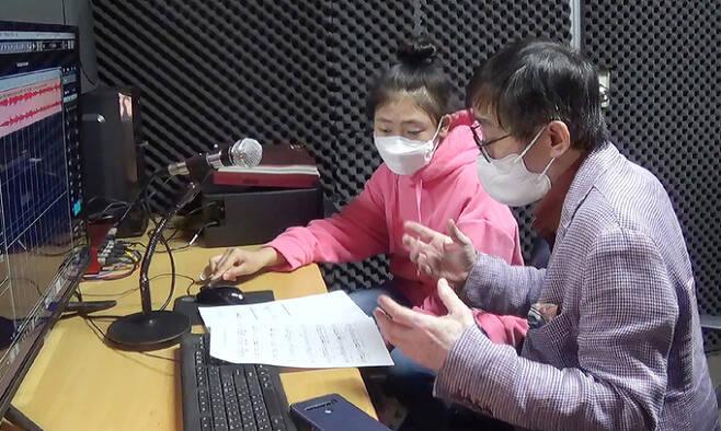 """'미얀마의 봄'을 시작으로 미얀마 사람들을 위한 헌정곡 프로젝트를 진행 중인 우주명 작곡가는 11일 인터뷰에서 """"우리와 비슷한 아픔을 겪고 있는 미얀마 사람들에게 조금이나마 도움이 되기를 바란다""""고 말했다. 사진은 우 작곡가와 미얀마 출신 가수 완이화가 노래를 녹음하고 있는 모습. 풀피리 프로젝트 제공"""