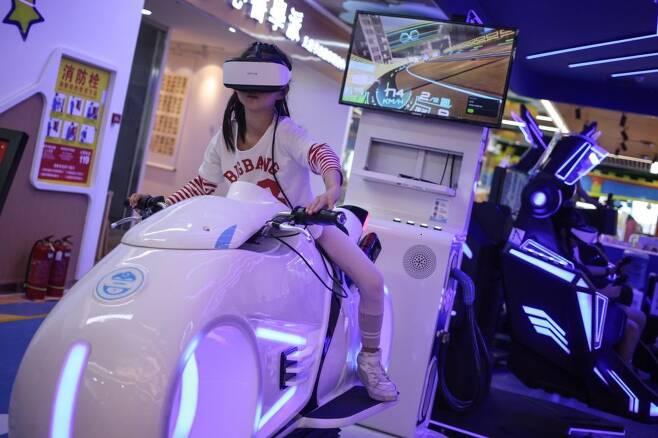한 여자 아이가 6월1일 베이징의 한 쇼핑몰에서 가상현실 게임을 즐기고 있다. 중국은 전날인 5월31일 세자녀 출산 허용 정책을 발표했다. /EPA 연합뉴스
