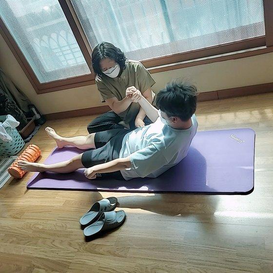 김호영(오른쪽)씨가 대한작업치료사협회 부회장과 함께 재활에 힘쓰고 있다. 사진 김두경씨 제공