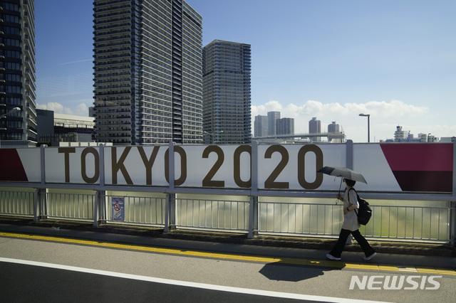 [도쿄=AP/뉴시스] 17일 한 여성이 '도쿄 올림픽 2020' 현수막이 붙어 있는 도쿄의 한 교량을 지나고 있다. 2021.07.17.