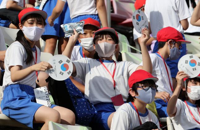 미카사 초등학교 학생들이 태극기가 그려진 부채를 흔들며 한국 선수들을 응원하고 있다. 경기가 열리는 가시마는 긴급 사태 지역에 포함되지 않아 관중이 들어올 수 있다. 사진| 연합뉴스