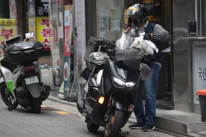 수도권의 '사회적 거리두기'가 4단계로 격상된 지 1주일이 된 19일 점심시간 서울 종로구 관철동 젊음의거리 식당가에서 라이더들이 배달을 나서고 있다. /연합뉴스 제공