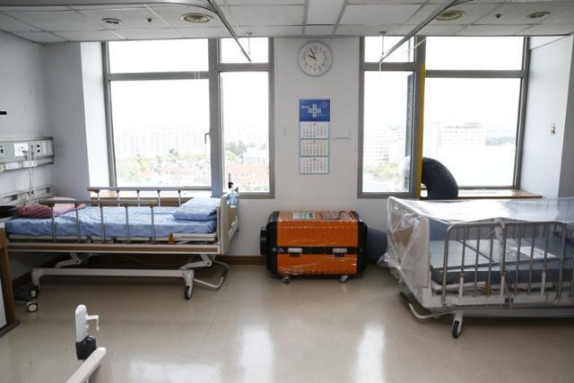 경기 고양시 국민건강보험공단 일산병원의 한 병실이 코로나19 전담병상으로 전환할 준비를 하고 있다. 가운데 놓인 주황색 설비가 병실 안 공기가 밖으로 나가지 못하게 막는 음압장치다. 일산병원 제공