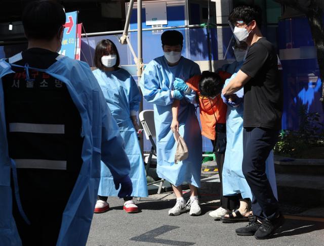 22일 오전 폭염 속에 서울시내 한 선별진료소에서 신종 코로나바이러스 감염증(코로나19) 검사를 기다리던 시민이 쓰러지자 의료진이 응급차로 이송하고 있다. 뉴스1