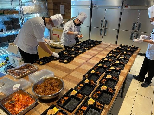 일본 도쿄올림픽에 출전한 한국 선수단을 지원하는 대한체육회의 현지 급식지원센터에서 20일 조리사들이 음식을 도시락 용기에 담고 있다. 연합뉴스