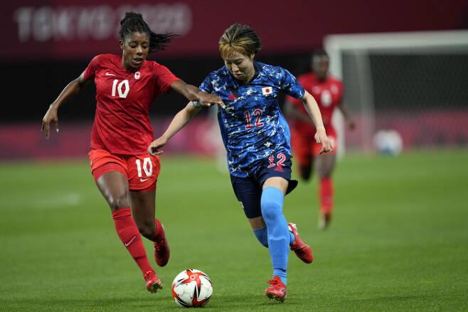 일본 여자 축구 대표팀 준 엔도(오른쪽)가 21일 캐나다와의 도쿄 올림픽 조별리그 1차전에서 드리블을 하고 있다.   AP연합뉴스