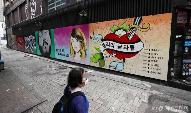 29일 서울 종로의 한 골목에 윤석열 전 검찰총장의 아내 김건희씨를 비방하는 내용의 벽화가 그려져 있다. 한 시민이 벽화를 바라보고 있다. /사진=김휘선 기자 hwijpg@