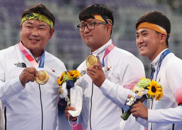 2020 도쿄올림픽 남자 양궁 단체전에서 금메달을 차지한 김제덕(오른쪽부터), 김우진, 오진혁이 26일 도쿄 유메노시마 공원 양궁장에서 시상식을 마친 후 기념 사진을 찍고 있다. 연합뉴스