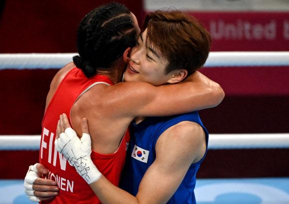 30일 일본 코쿠기칸(國技館)에서 열린 도쿄올림픽 여자 복싱 라이트급 16강전이 끝난 뒤 한국의 오연지(오른쪽)와 핀란드의 미라 포트코넨이 포옹을 하고 있다. AFP 연합뉴스