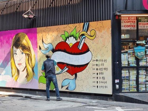 대선 주자인 윤석열 전 검찰총장의 부인 김건희씨를 연상케 해 논란이 된 서울 종로구의 한 중고서점 벽화의 문구를 30일 서점 직원이 지우고 있다. 조해언 인턴기자