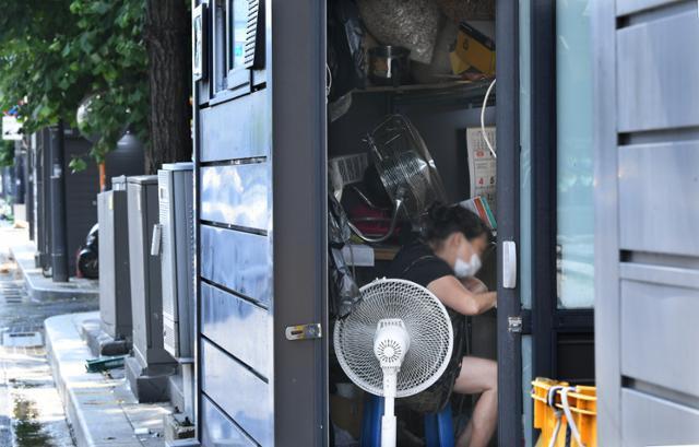 3일 오후 종로구 창신동 동대문역 부근의 '거리 가게' 안에서 한 상인이 선풍기 바람에 의존해 더위를 식히고 있다. 왕태석 선임기자