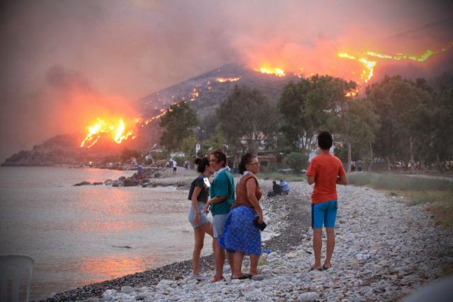 터키에서 수십 년 만에 발생한 최악의 산불이 발생한 가운데 3일 밀라스 인근 에게해 연안도시 오렌 언덕 위로 불길이 번지는 것을 해변에 있던 사람들이 지켜보고 있다. /AFP연합뉴스