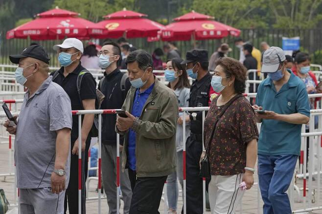"""[베이징=AP/뉴시스]2일 중국 베이징에서 코로나19 확산을 막기 위해 마스크를 쓴 시민들이 중국의약집단 시노팜 백신을 접종하기 위해 줄 서 있다. 중국 외교부는 """"국내 백신 공급이 부족한 상황에도 국제사회에 3억5000만 회분 이상의 코로나19 백신을 제공했다""""라고 밝혔다. 2021.06.02."""