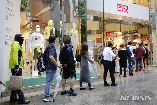 [도쿄=AP/뉴시스]지난해 6월 19일 일본 도쿄 긴자 거리에 위치한 유니클로 매장에 입장하기 위해 시민들이 줄을 서서 기다리고 있다. 2021.08.05.