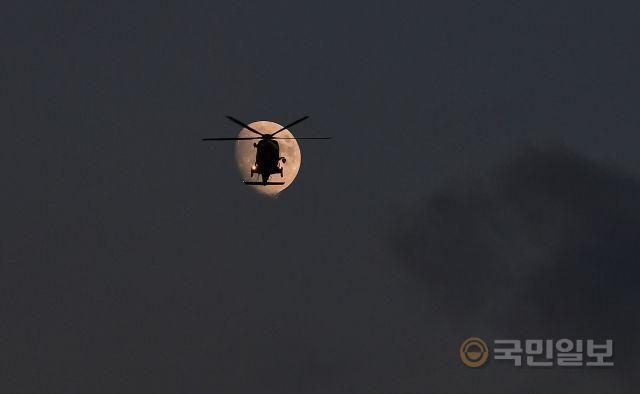 지난달 19일 인천 영종도 하늘에서 밝게 뜬 달 앞으로 해경 구조헬기가 순찰 비행을 하고 있다.