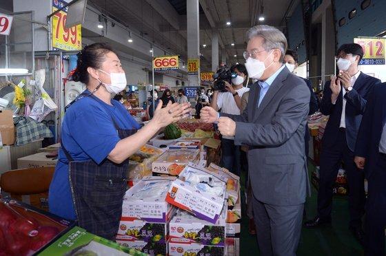 더불어민주당 대권 주자인 이재명 경기도지사가 추석 연휴 첫날인 지난 18일 오후 광주 서부 농수산물도매시장 청과물동을 찾아 지지자들과 인사를 나누고 있다. 뉴스1